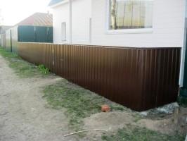 Сплошной забор из профнастила Прушиньски, сверху установлена заборная планка.